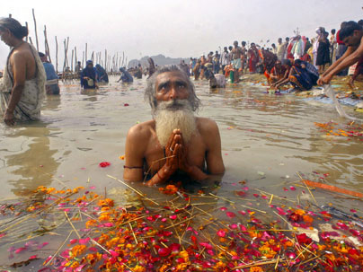 holy man prays in the ganges river during magh
